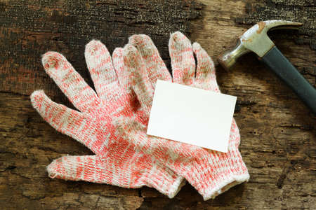 odd jobs: Working cloth gloves, a piece of paper and hammer on wooden table. Concepts.