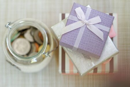 Striped, silver and purple gift boxes stacked together beside glass jar filled with coins on textured background. Selective focus to emphasize. Concept of saving for present or special occasion