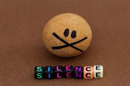 guardar silencio: bola marrón pintado con ojos negros y la boca con cinta adhesiva SILENCIO palabra delante de él Foto de archivo