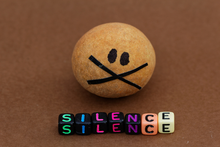 backdoor: Brown ball painted with black eyes and taped mouth with word SILENCE in front of it