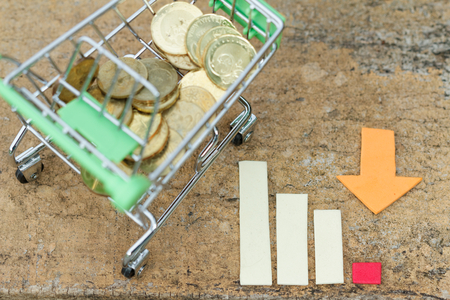 purchasing power: Trolley filled with coins beside chart showing decreasing trend. Concept of decline in business,spending and purchasing power,economy. Concept of inflation. Concept of financial issue.