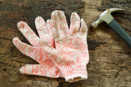 odd jobs: Working cloth gloves and hammer on wooden table. Concepts.