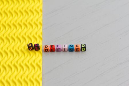 Plastic alphabet block arranged to form word REDEFINED. Two different texture represent the word redefined. Stock Photo
