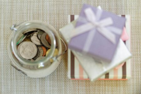 emphasize: Striped, silver and purple gift boxes stacked together beside glass jar filled with coins on textured background. Selective focus to emphasize. Concept of saving for present or special occasion Stock Photo
