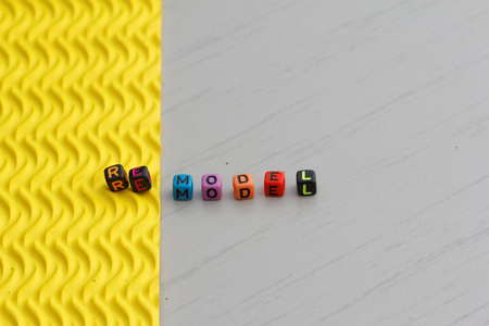 reevaluation: Plastic alphabet block arranged to form word REMODEL. Two different texture represent the word remodel. Change from one texture to another different texture. Concept.