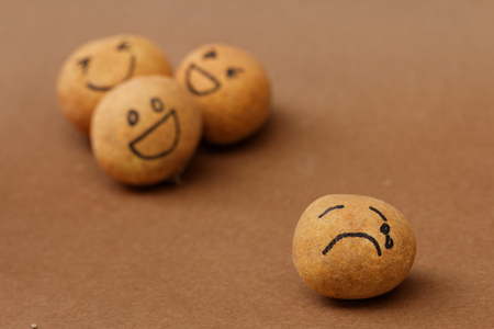 A group of brown ball laughing in the background while the brown ball in front alone and look sad and depressed. Concept of discrimination,bully,mental illness. Stock Photo