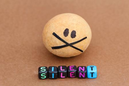 guardar silencio: bola marrón pintado con ojos negros y la boca con la palabra grabada SILENT frente a ella