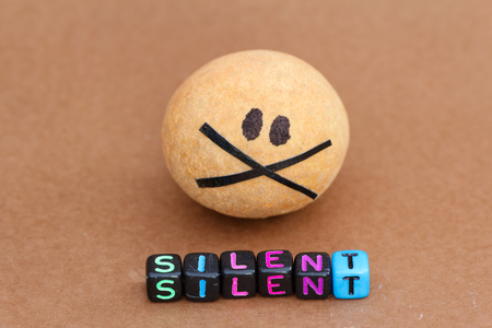 silent: Brown ball painted with black eyes and taped mouth with word SILENT in front of it