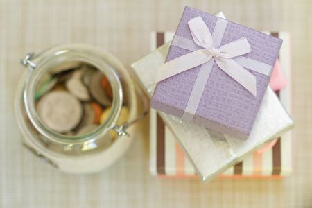 emphasize: Striped, silver and purple gift boxes stacked together beside glass jar filled with coins on textured background. Selective focus to emphasize. Concept of saving for present or special occasion.