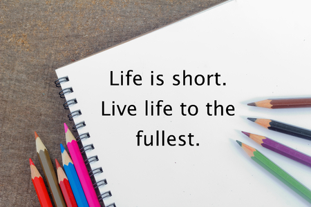 short phrase: Blank notepad and colorful pencils on the wooden table. View from above. With phrase Life is short. Live life to the fullest.