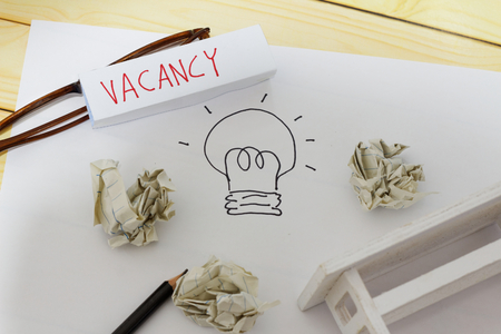 Vacancy and employment concept. White paper with drawing of a light bulb, crumpled papers, glasses, pencil, mini toy table and word VACANCY written on a small piece of paper.