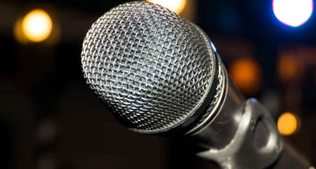Silver microphone on microphone stand with blurred glowing background Фото со стока