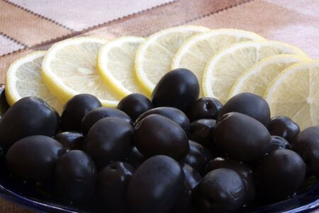 black olive with lemon segments on plate