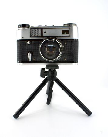 old-fashioned photographic camera on mini-tripod against white background Stock Photo