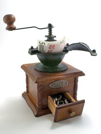 grind: handmill moler dinero y gire a la moneda  Foto de archivo