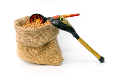 bag with buckwheat and wooden spoons photo