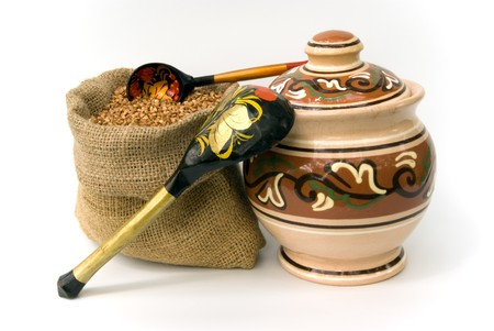 bag with buckwheat and wooden spoons and ceramic pot photo