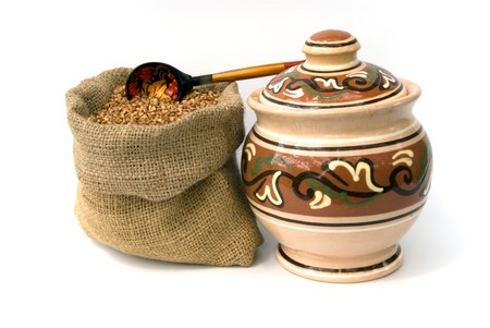 bag with buckwheat and wooden spoon and ceramic pot photo