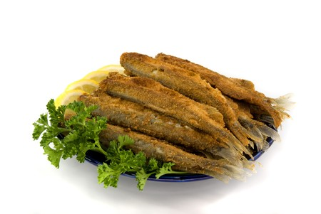 fried small fish on the plate photo