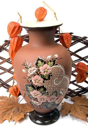 vase and autumn plant on wickerwork photo