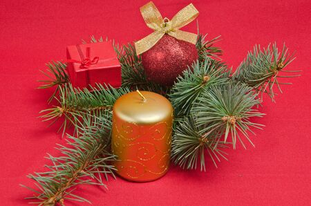 christmas decorations with candle and spruce on red photo