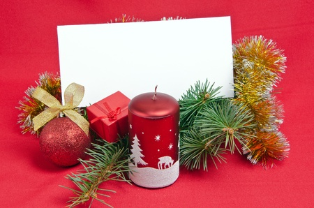 christmas decorations with candle and card on red photo