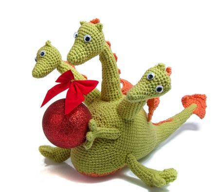 christmas dragon: toy as knitted dragon with christmas ball Stock Photo