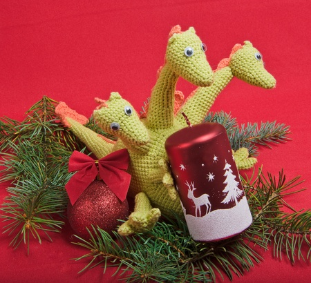 christmas dragon: christmas decorations as dragon with candle on red