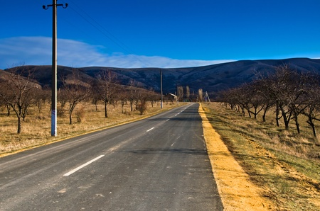 country asphalt road leading into the mountains photo