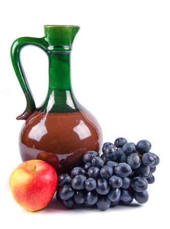 old ceramic decanter with grapes on white background photo