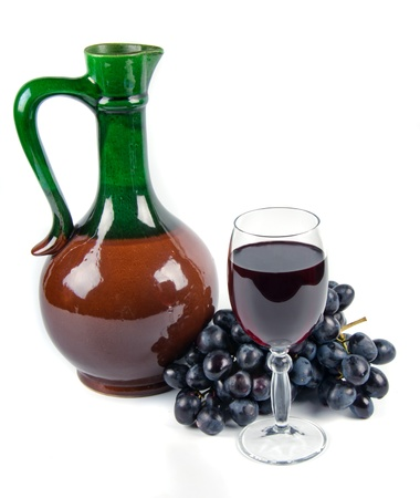 old ceramic decanter and glass with wine on white background photo