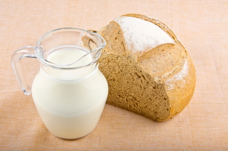 bread and milk in pitcher on tablecloth photo
