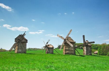ancient windmills in field against sky photo