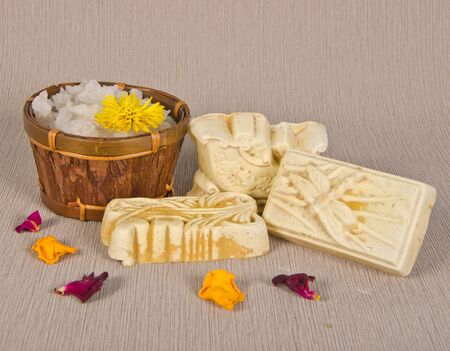 handmade soap and salt with petals on grey background photo