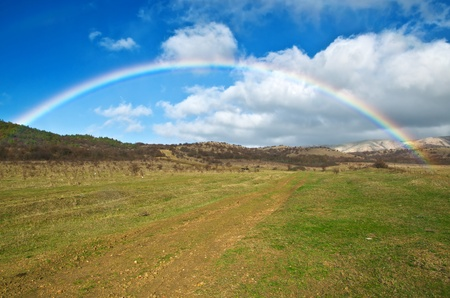 miracle tree: Full rainbow over autumn field against the clouds