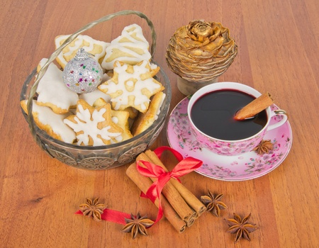 mulled wine with christmas cookies and pinecone and spice on table photo