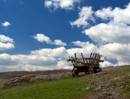 cartage: deserted cart on grass against mountain Stock Photo