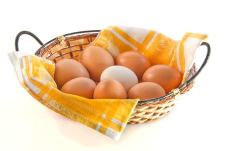 servilleta de papel: huevos en la cesta de mimbre con servilleta amarilla sobre fondo blanco
