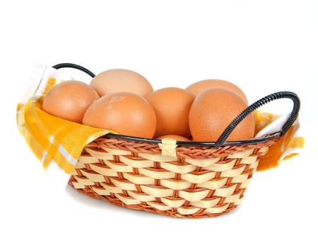 Serviette: huevos en la cesta de mimbre con servilleta amarilla sobre fondo blanco