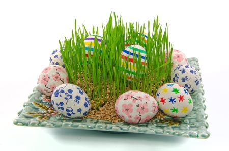 Easter eggs and wheat grass on a plate photo