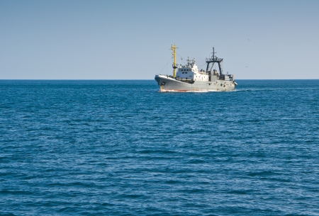fishing trawler floating in the sea Stock Photo