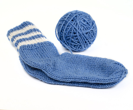 knitted socks from woolen thread and skein of thread on a white background