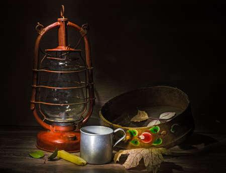 kerosene lamp: kerosene lamp and antiques on wooden table in dark