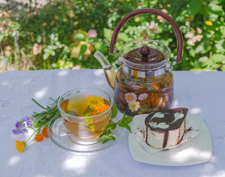 Herbal tea and chocolate cake on a table in the garden Stock Photo