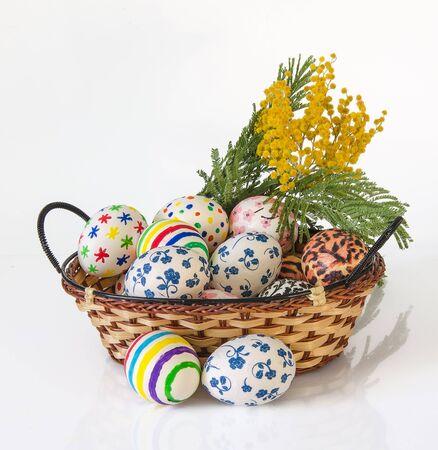 white eggs: Easter eggs in wicker basket and flower on white background