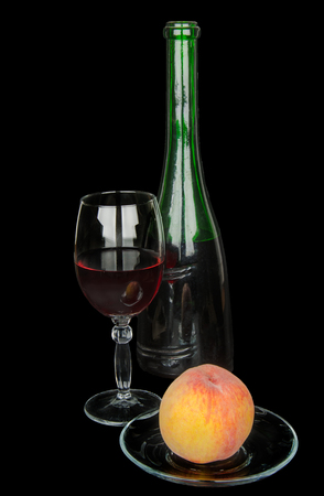 taster: glass of wine and peach on black background
