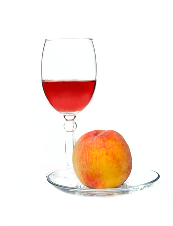 glass of wine and peach on white background