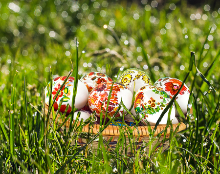 Easter eggs in wicker basket in grass