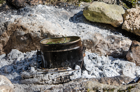 camping pot of tea on coals from a fire Stock Photo