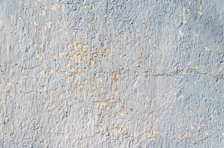 grey peeling paint on the old rough concrete surface as background Stock Photo